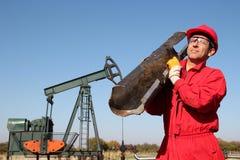 De Olieveldarbeider bij goed Pomp Jack Site. Royalty-vrije Stock Afbeelding