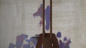 De olieverven worden toegepast met een borstel op de canvas achtermening stock video