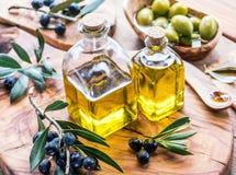 De olijfolie en de bessen zijn op het olijf houten dienblad royalty-vrije stock afbeeldingen