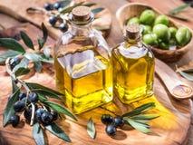 De olijfolie en de bessen zijn op het olijf houten dienblad royalty-vrije stock fotografie