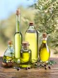 De olijfolie en de bessen zijn op de houten lijst stock afbeelding