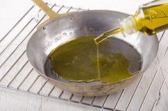 De olijfolie wordt gegoten in een pan Royalty-vrije Stock Afbeeldingen