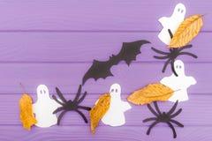 De olika pappers- konturerna för slagträ, för spökar och för spindlar med höstsidor som göras av halloween hörnram Arkivbild