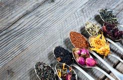 De olika sorterna av te som framläggas som en prövkopia i silverskedarna, bästa sikt arkivbilder