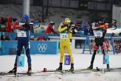 De olympische kampioen Martin Fourcade van Frankrijk concurreert in het de massabegin van biathlonmensen ` s 15km bij 2018 de Win stock foto