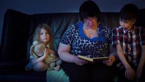 De oma leest thuis een boek voor kleinkinderen stock video