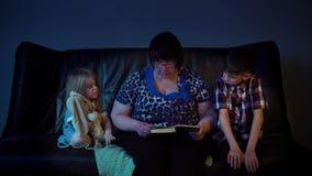 De oma leest thuis een boek voor kleinkinderen stock footage