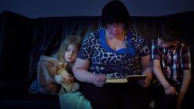 De oma leest thuis een boek voor kleinkinderen stock videobeelden