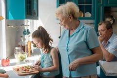 De oma onderwijst kleindochter aan kok royalty-vrije stock afbeeldingen