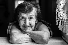 De oma zit dichtbij het venster in de keuken Stock Foto's