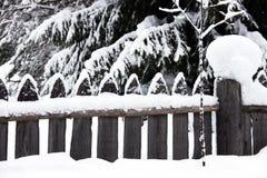 De omheining in de sneeuw Sneeuwomheining in het dorp Karelië Stock Foto's