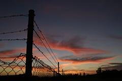 De Omheining van de Draad van de weerhaak bij Zonsondergang Stock Foto's