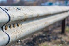 De omheining van de metaalweg dichtbij de oude stadsweg Royalty-vrije Stock Foto's