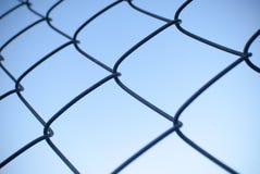 De omheining van het draadnetwerk met blauwe hemelachtergrond Stock Foto's