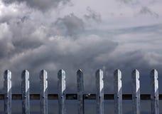 De omheining van het metaal met donkere wolken stock afbeelding