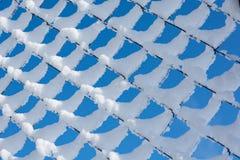 De omheining van het metaalgaas met cellen de ketting-verbinding met sneeuw wordt behandeld die royalty-vrije stock afbeelding
