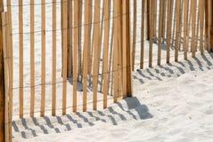 De omheining van het piket op wit zandstrand. stock afbeelding