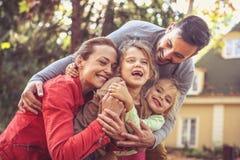 De omhelzing van de familiegroep Het seizoen van de herfst Weg in dalingsbos royalty-vrije stock afbeelding
