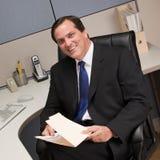 De omslag van het de holdingsdossier van de zakenman bij bureau in cel Royalty-vrije Stock Foto
