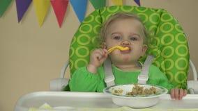 De onafhankelijke babyjongen met lepel zit bij het voeden van stoel en eet havermoutpap stock footage