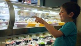 De onafhankelijke weinig jongen dichtbij showcase kiest diner op een bewegende transportbandlijn met verschillend voedsel in de k stock video