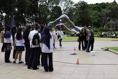 De onbekende straatkunstenaar maakt grote zeepbels met twee stokken en draad voor groep vrouwen in Hyde Park Stock Foto's