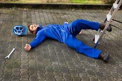 De onbewuste technicus viel van ladder op straat Royalty-vrije Stock Afbeeldingen