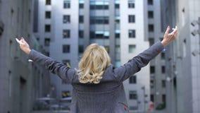 De onbezorgde blonde vrouw die in formeel kostuum handen opheffen steunt mening, vrouwelijke wellness stock videobeelden