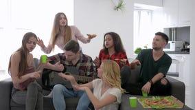 De onbezorgde groep vrienden die partij hebben thuis, de jeugd heeft pret en zingt met een gitaarzitting op de bank stock footage