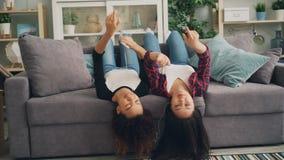 De onbezorgde jonge vrouwen luisteren aan muziek door oortelefoons gebruikend zich smartphone en het dansen het liggen op bank en stock footage
