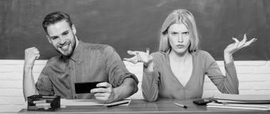 De onbezorgde kerel en het meisje zitten bij bureau in klaslokaal Het bestuderen op hogeschool of universiteit Vriendenstudenten  stock foto
