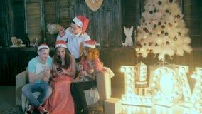 De onbezorgde Tienervrienden vieren Kerstmis dichtbij Verfraaid Kerstmis het letten op video'ssmartphone stock videobeelden