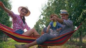 De onbezorgde vakanties, familiezitting op hangmat werpen appelen en heffen vreugdevol hun op indient mooie tuin stock footage