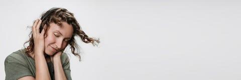 De onbezorgde vrolijke jonge krullende vrouw luistert favoriete muziek met haar stereohoofdtelefoons stock foto