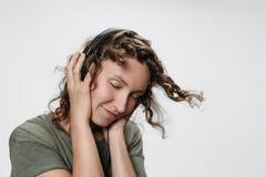 De onbezorgde vrolijke jonge krullende vrouw luistert favoriete muziek met hand op haar hoofdtelefoons stock afbeelding