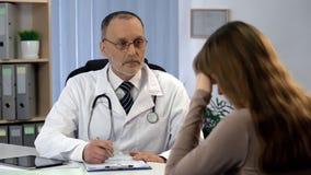 De oncoloog die vrouw informeren over ongeneeslijke ziekte, patiënt voelt gedeprimeerd stock afbeelding
