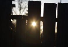 De onderbrekingen van de ochtendzon door een gat in omheining stock afbeelding