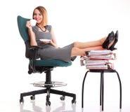 De onderbrekingsonderneemster van het vrouwenwerk het ontspannen benen op overvloed van doc. Stock Afbeelding