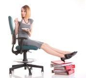 De onderbrekingsonderneemster van het vrouwenwerk het ontspannen benen op overvloed van doc. Royalty-vrije Stock Foto's