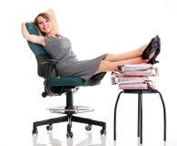 De onderbrekingsonderneemster van het vrouwenwerk het ontspannen benen op overvloed van doc. Stock Foto's