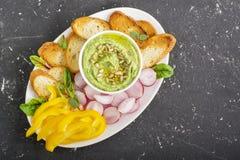 De onderdompeling van de avocadoyoghurt, gesneden verse groenten, kernachtig brood op een plaat Hoogste mening royalty-vrije stock afbeelding