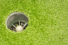 De ondergedompelde bal in golf ligt in het gat op green stock foto's