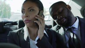 De onderneemster die op telefoon op auto achterbank spreken, mens die haar hand houden, hield de mens stock videobeelden