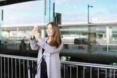 De onderneemster die van Nice selfie door dichtbijgelegen smartphone maken valise en luchthaven royalty-vrije stock foto's