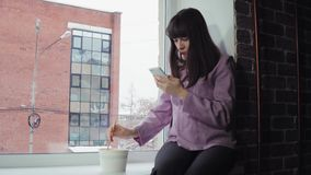 De onderneemster eet onmiddellijke noedels zittend op vensterbank tegen de baksteenbouw stock videobeelden