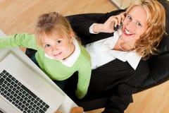 De onderneemster en de moeder werken in de intern Royalty-vrije Stock Afbeelding