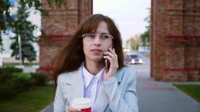 De onderneemster in glazen in licht kostuum gaat werken, drinkt het meisje koffie en spreekt op smartphone stock video