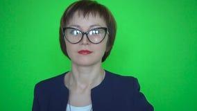 De onderneemster in kostuum en glazen danst op groene het schermachtergrond stock videobeelden