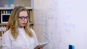 De onderneemster maakt een presentatie in het bureau Schrijft teller op een witte raad stock videobeelden