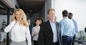 De onderneemster maakt telefoongesprek lopend met gelukkig glimlachend bedrijfsmensenteam in modern creatief bureau